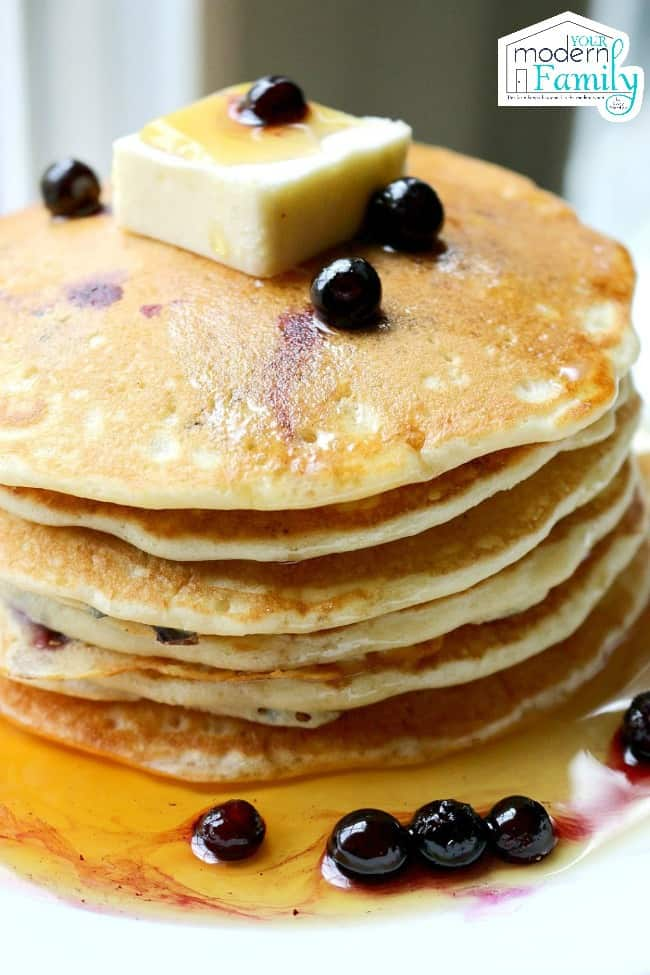 A close up of a stack of blueberry pancakes with butter on top.
