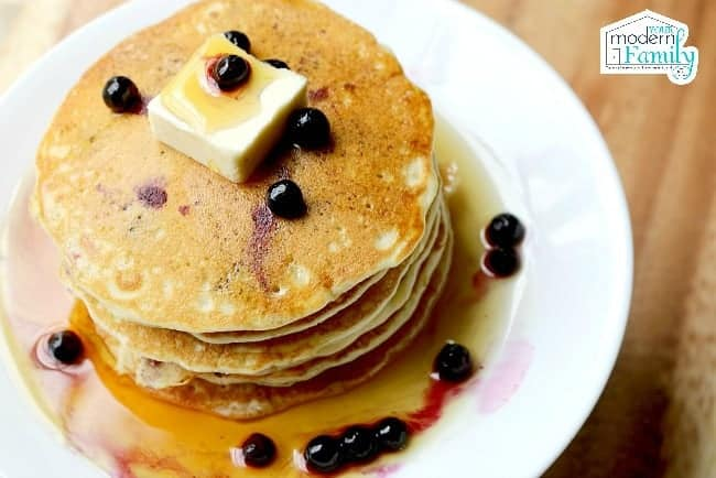 A stack of Blueberry pancakes with syrup and butter on a white plate.