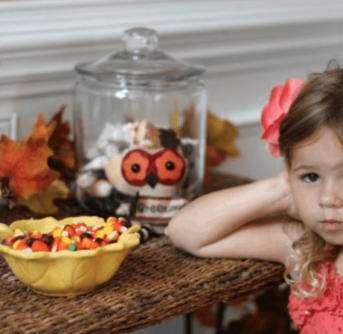 A little girl sitting at a table with a bowl of Halloween candy and a glass jar behind her.