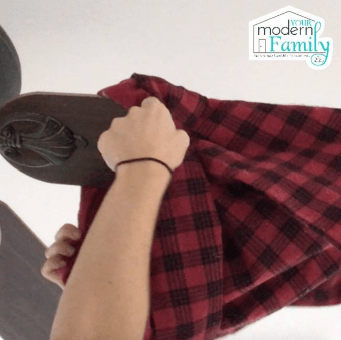 A person using a flannel shirt to clean ceiling fan blades.