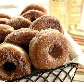 A basket of doughnuts sitting on a table.