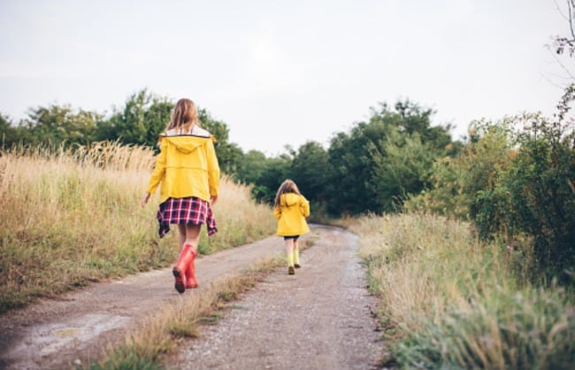 Two little girls walking down a dirt road