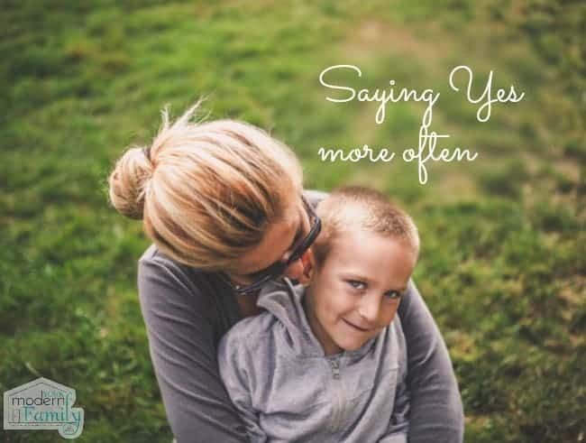 A woman holding a boy on her lap in the grass with text above them.