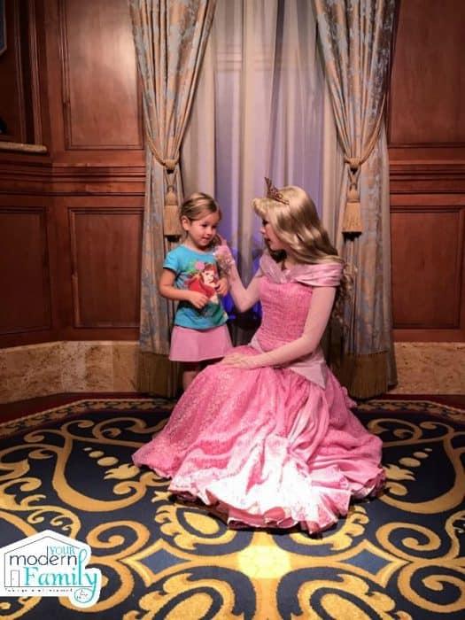 A little girl meeting a princess.