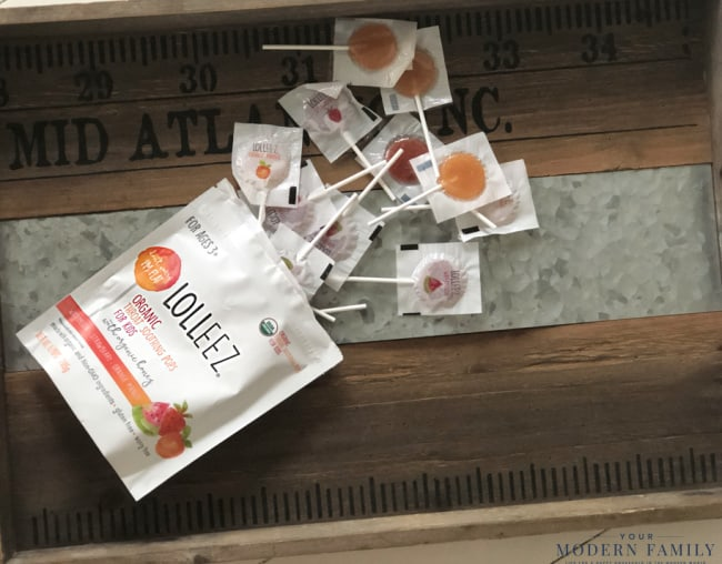 A wooden cutting board with Lolleez sore throat lollipops.