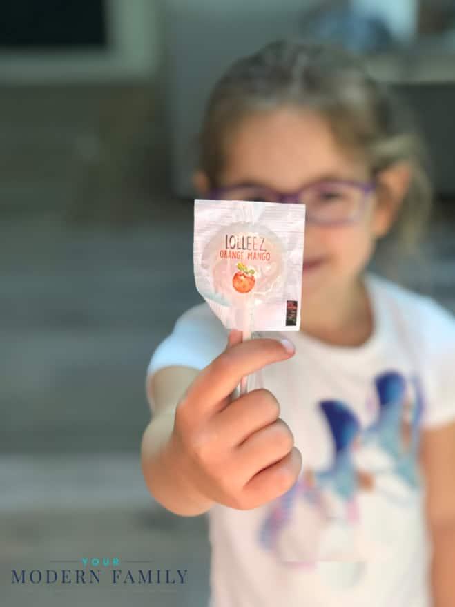 A little girl holding a lollipop.