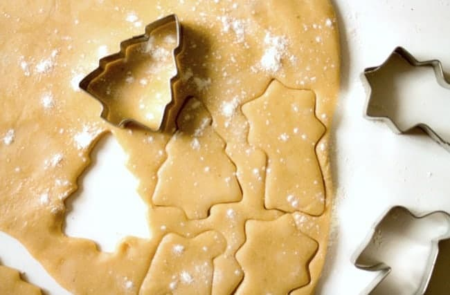 Rolled out cookie dough with a Christmas tree cookie cutter resting on it.