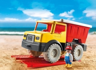 A toy truck and driver on the sand.