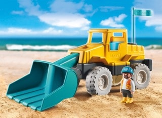 A toy tractor on a beach.
