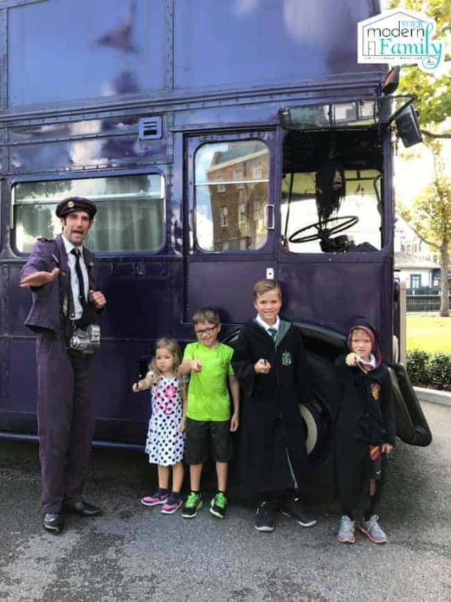 A group of people in costumes standing in front of a bus.