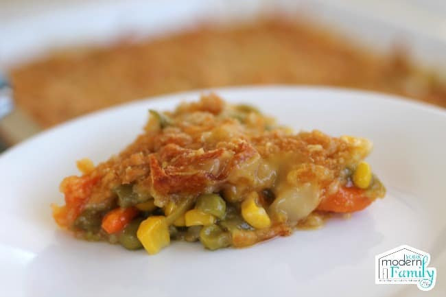 A white plate of baked Vegetable Casserole with Cheesy Topping.