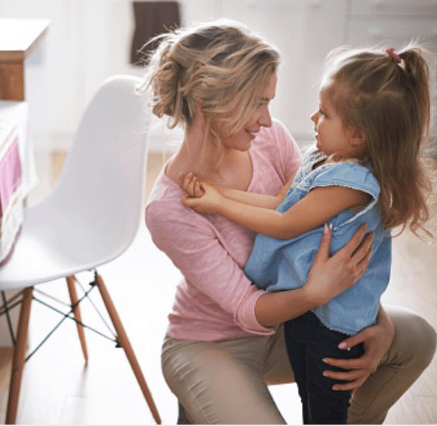 A woman kneeling down hugging a little girl.
