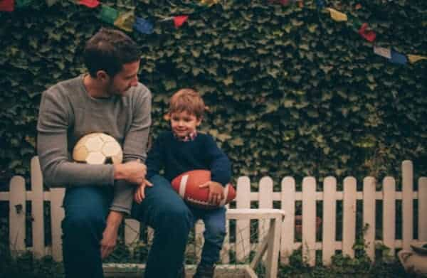 A man sitting on a bench with a little boy holding a football.