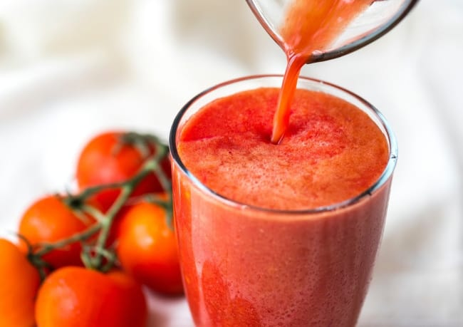 A close up of a glass of tomato juice