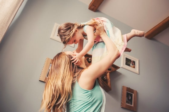 A woman holding a young girl up in the air.
