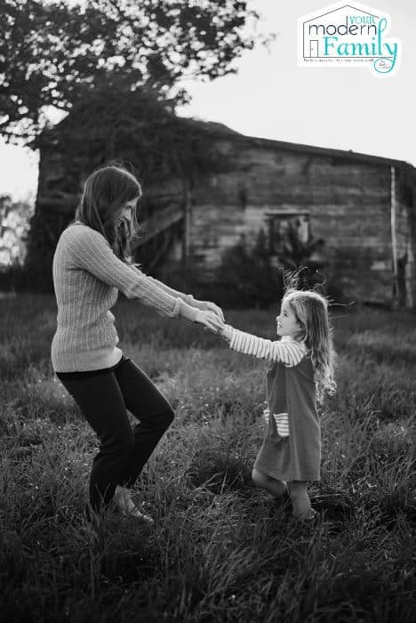 A lady and a little girl holding hands in front of a barn.