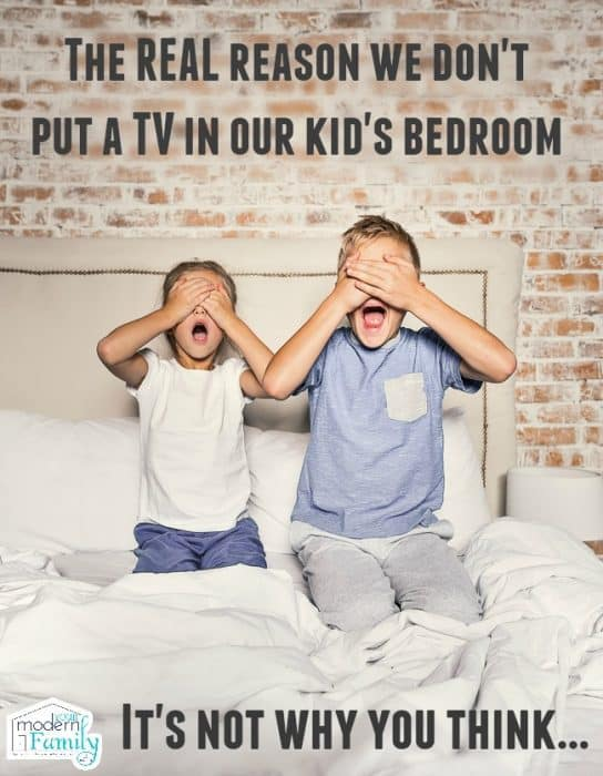 Two children kneeling on a bed with their hands covering their eyes and their mouths open.