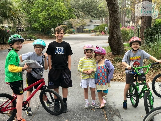 A group of kids standing by bicycles.