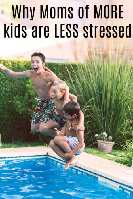 Three boys jumping in a pool of water.