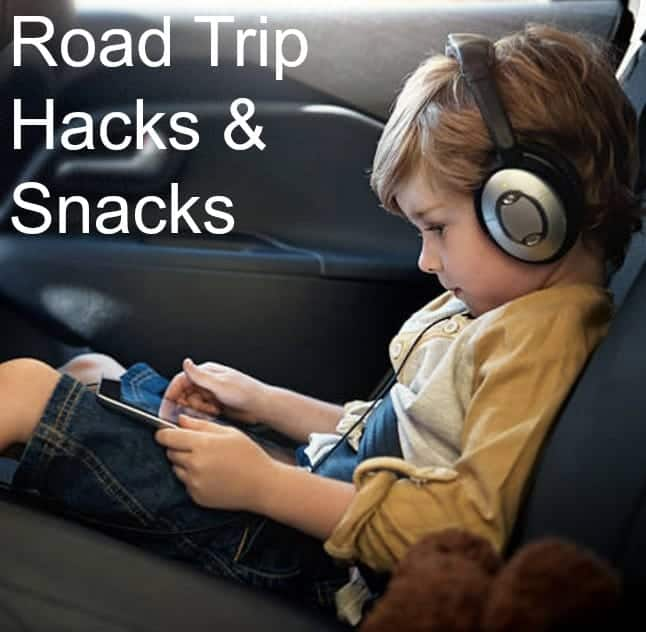 A little boy sitting in a car looking at a cell phone with head phones on.