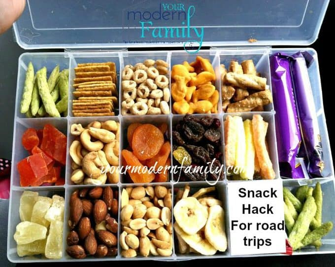 A plastic container with dividers filled with different types of food for traveling.