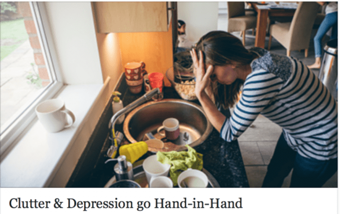 A woman leaning on a kitchen counter with clutter around her as she holds her head in her hands.