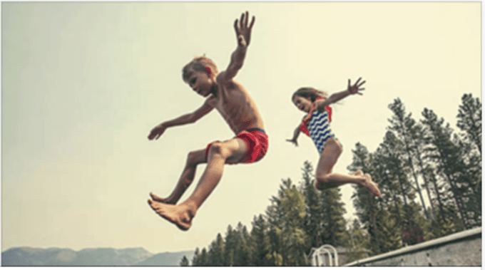 Two kids  jumping in the air.