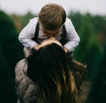 A woman lifting a child up to kiss him.