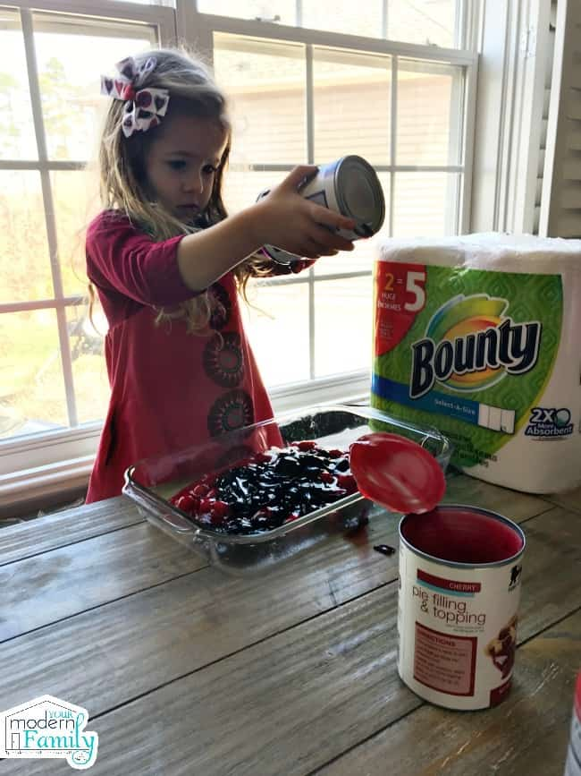 A little girl pouring a can of pie filling into a glass tray with a package of Bounty paper towels beside her.