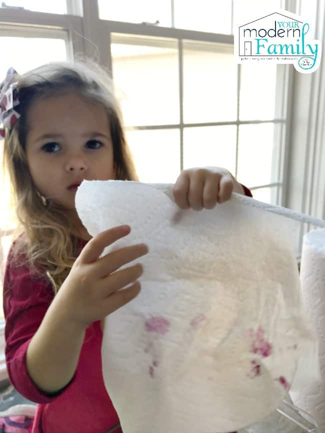 A little girl wiping her dirty hands on a Bounty paper towel.