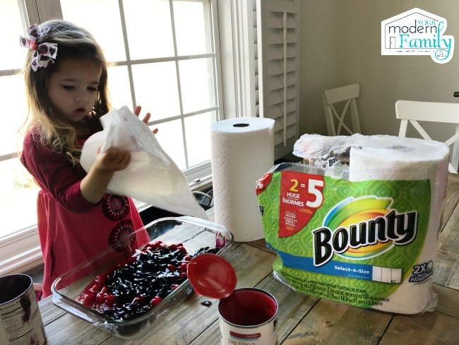 A little girl making a dump cake and wiping her hands with a Bounty paper towel.