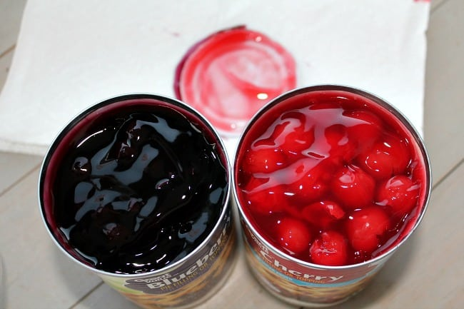 Two open cans of fruit pie filling on a table.