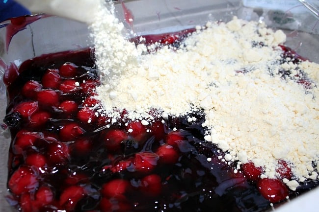 Someone pouring cake mix on top of fruit pie filling.