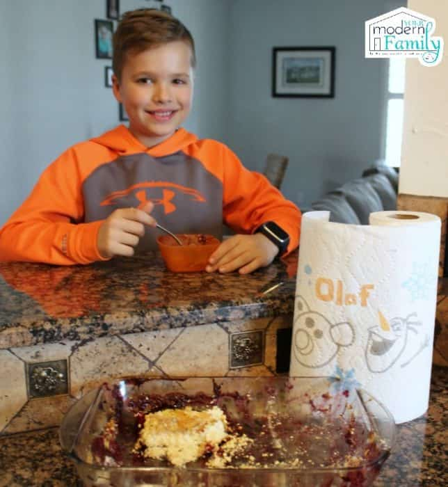 A little boy sitting at a table eating Dump Cake with a roll of Bounty paper towels beside him.