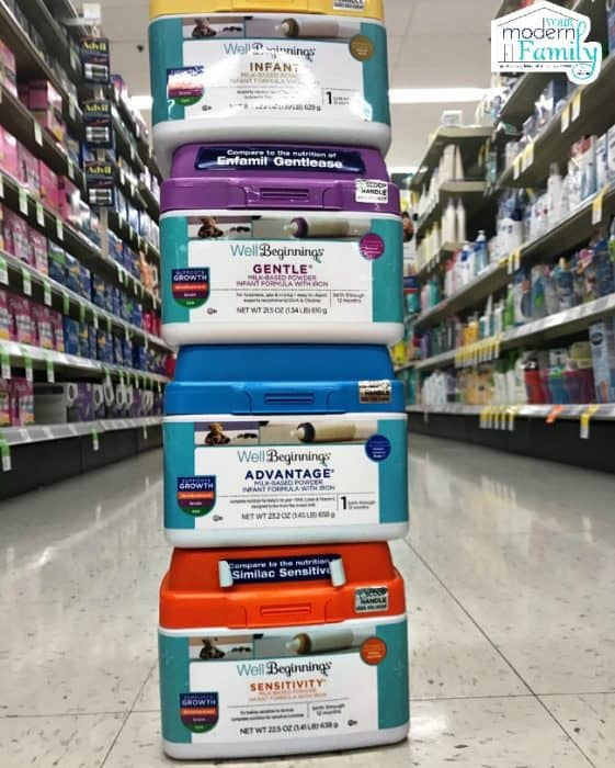 A close up of baby formula containers stacked on top of each other in a store isle.