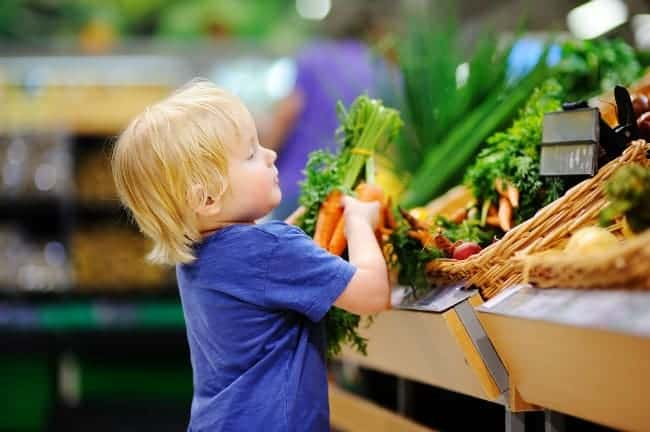 A little boy getting carrots from a vegetable stand in a grocery store.