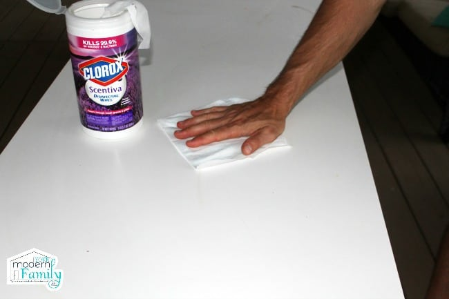 A person cleaning the counter with Clorox wipes.