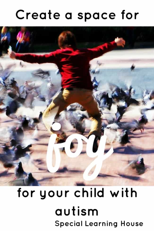 A boy waving his arms with pigeons flying away from him.