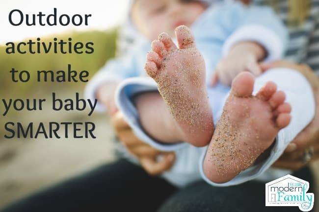 A baby\'s bare feet covered in sand.