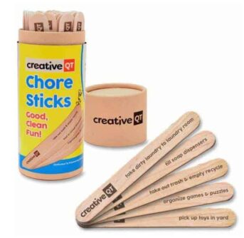 A container of Chore Sticks with a few sticks resting beside it.