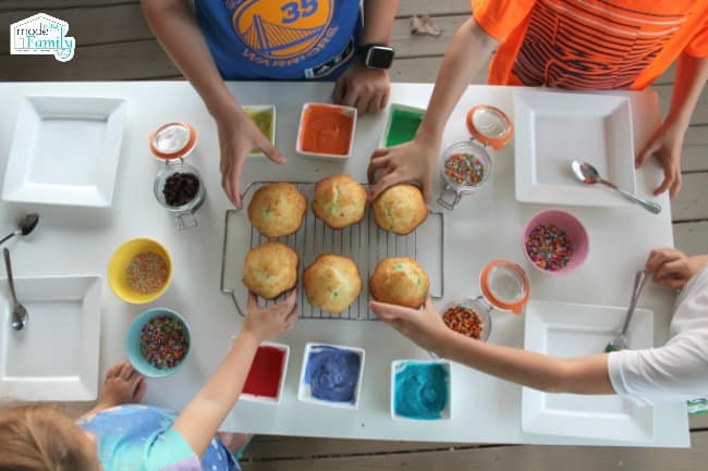A group of kids selecting a cupcake to decorate with different colors of icing and toppings on the table.