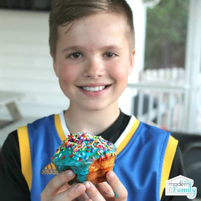 A young boy smiling at the camera while holding his decorated cupcake.