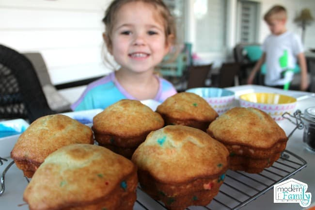 A little girl sitting at a table with a cooling rack of muffins in front of her.