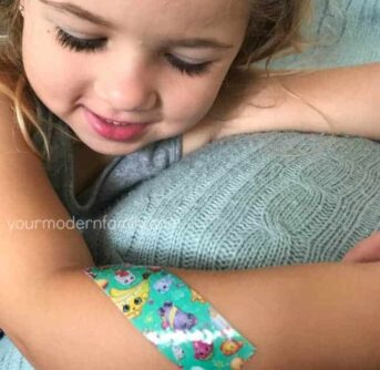 A close up of a girl with a band-aid on her arm.