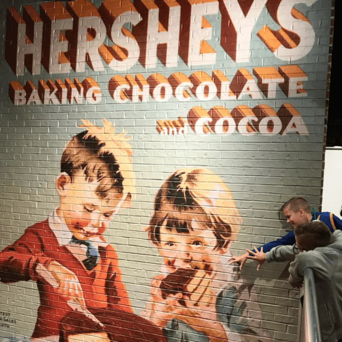 A brick wall painted with a mural of two kids eating cake.