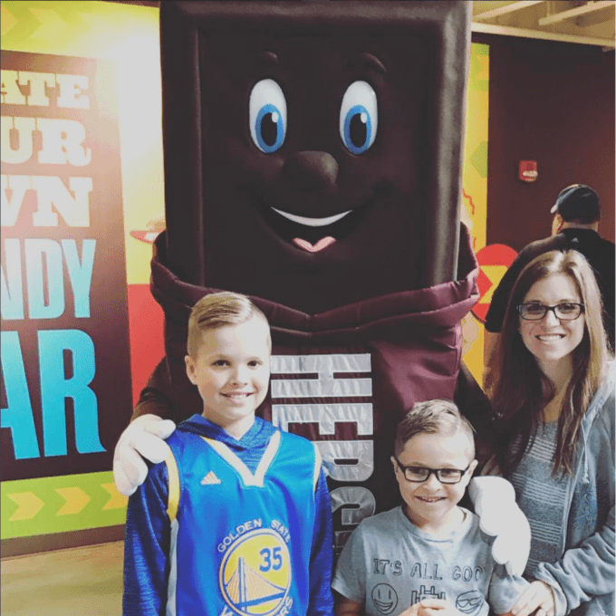 A group of people posing for the camera with a Hershey Chocolate Bar character.