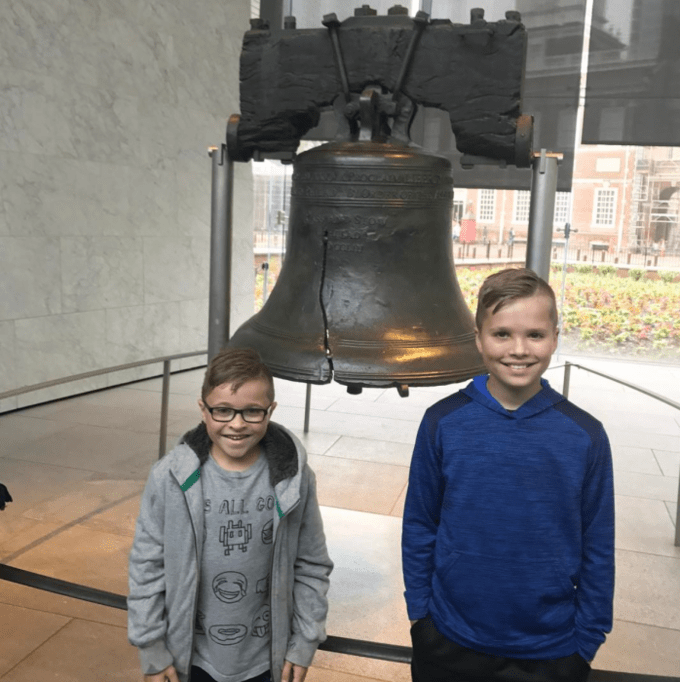 Two boys posing for the camera in front of the Liberty Bell.