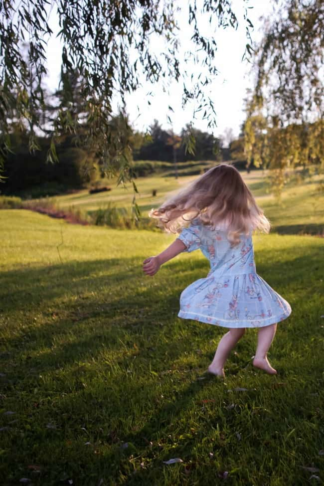 A little girl dancing in the grass.