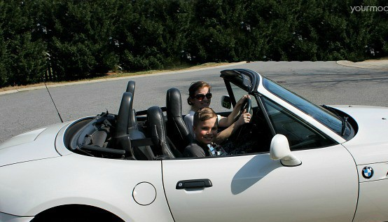 A woman and boy sitting in a convertible car.