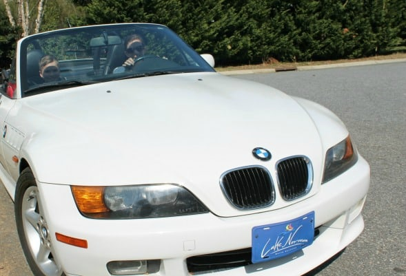 A front view of a woman in a convertible car.